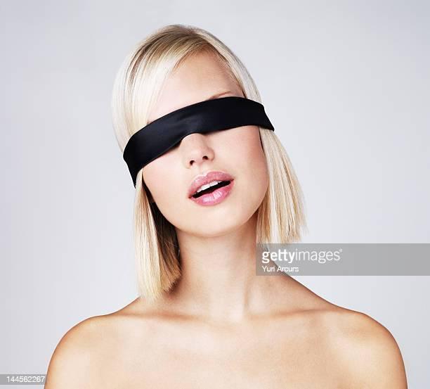 Young woman wearing blindfold, studio shot