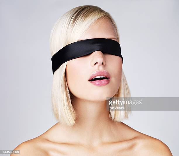 Young woman wearing blindfold, studio shot
