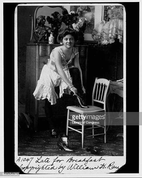 Young woman wearing bloomers and camisole with one foot on a chair tying her ankle boots