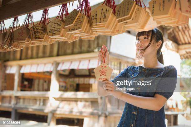 young woman wearing blue dress looking at wooden fortune telling plaques at shinto sakurai shrine, fukuoka, japan. - shinto shrine stock pictures, royalty-free photos & images