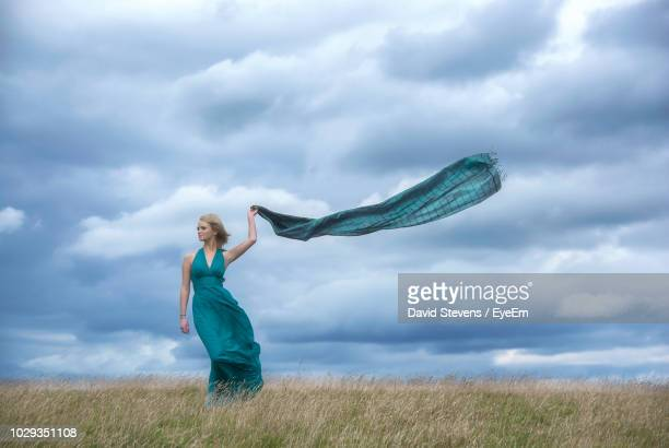 young woman wearing blue dress while standing on grassy field against cloudy sky - マフラー ストックフォトと画像