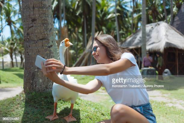 Young woman wearing blue  sunglasses taking a selfie with goose