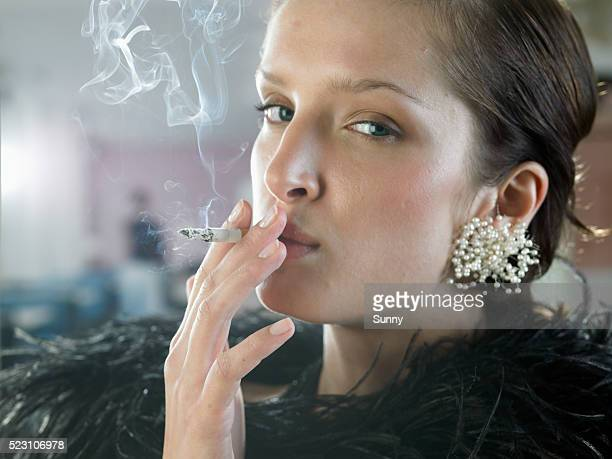 young woman wearing boa and earrings smoking - gier stock-fotos und bilder