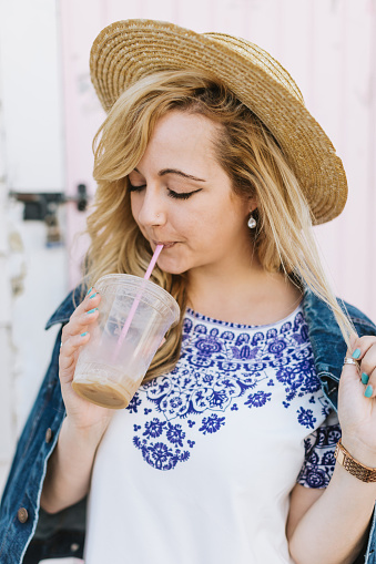 Young woman wearing boater drinking iced coffee from straw, Menemsha, Martha's Vineyard, Massachusetts, USA - gettyimageskorea