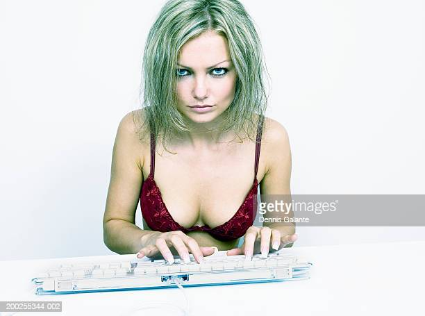 Young woman wearing bra typing on computer keyboard