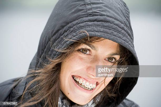 young woman wearing braces, outdoor portrait on a rainy day