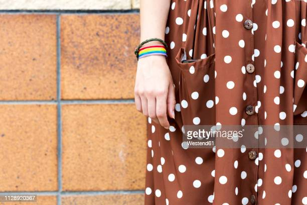 young woman wearing brown dress with white polka dots and wristband with prismatic colours, partial view - polka dot stock pictures, royalty-free photos & images