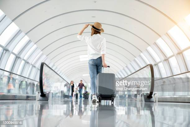 young woman wearing casual clothes and walking in the airport hall - travel destinations stock pictures, royalty-free photos & images