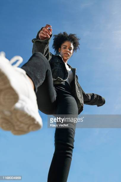 young woman wearing casuals against blue sky - posing shoes stock pictures, royalty-free photos & images