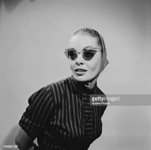 Young woman wearing cat's eye sunglasses with a headscarf, 1956.