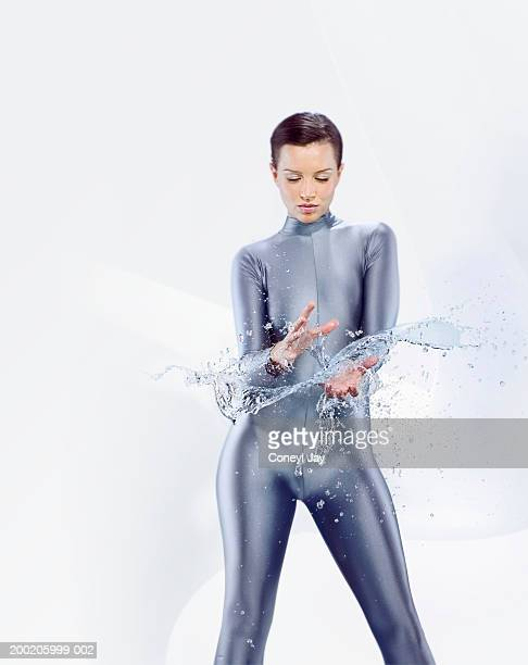 Young woman wearing catsuit with water between hands