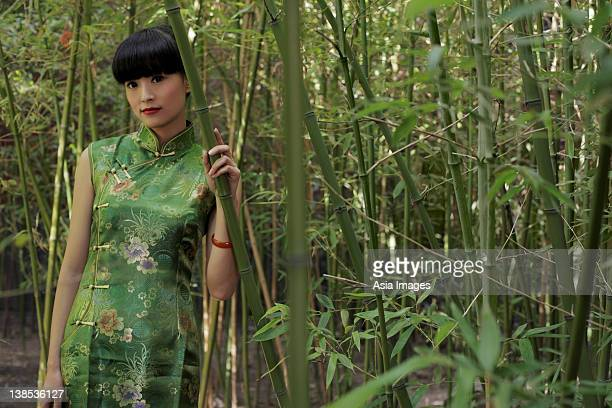Young woman wearing Chinese traditional dress standing in bamboo forest