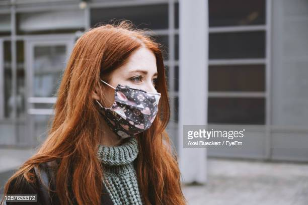 young woman wearing  cloth face mask outdoors   covid-19 corona , real people lifestyle in winter - hanover germany stock pictures, royalty-free photos & images