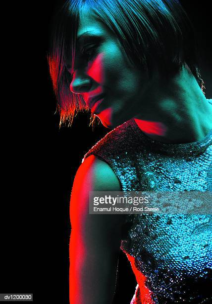 young woman wearing clubwear and looking sideways - gel effect lighting stock photos and pictures