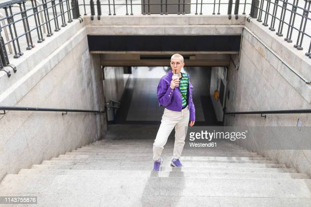 Young woman wearing colorful clothes standing on a staircase in the city