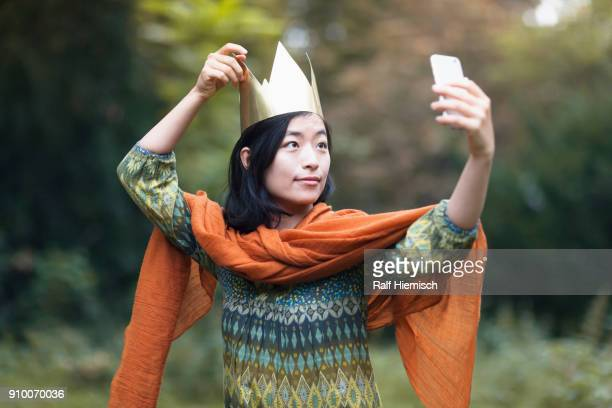 Young woman wearing crown taking selfie through mobile phone while standing at park