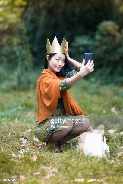 Young woman wearing crown taking selfie through mobile phone while crouching on field at park