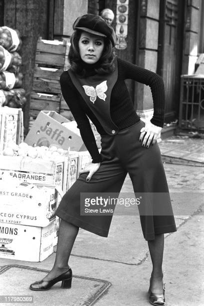 Young woman wearing culottes attached to a tabard-style top with a butterfly motif, in London's East End, circa 1970.