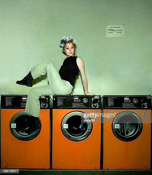 Mujer joven usando rulo de pelo en una peluquería sentado en Máquinas lavadoras