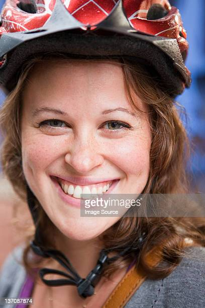 Young woman wearing cycle helmet, smiling