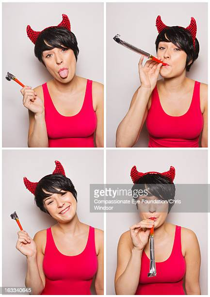 young woman wearing devil horns in photo booth - devil costume stock photos and pictures