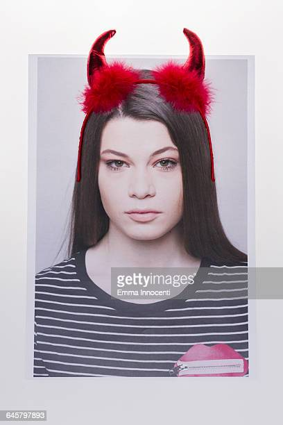 young woman wearing devil horns - devil costume stockfoto's en -beelden