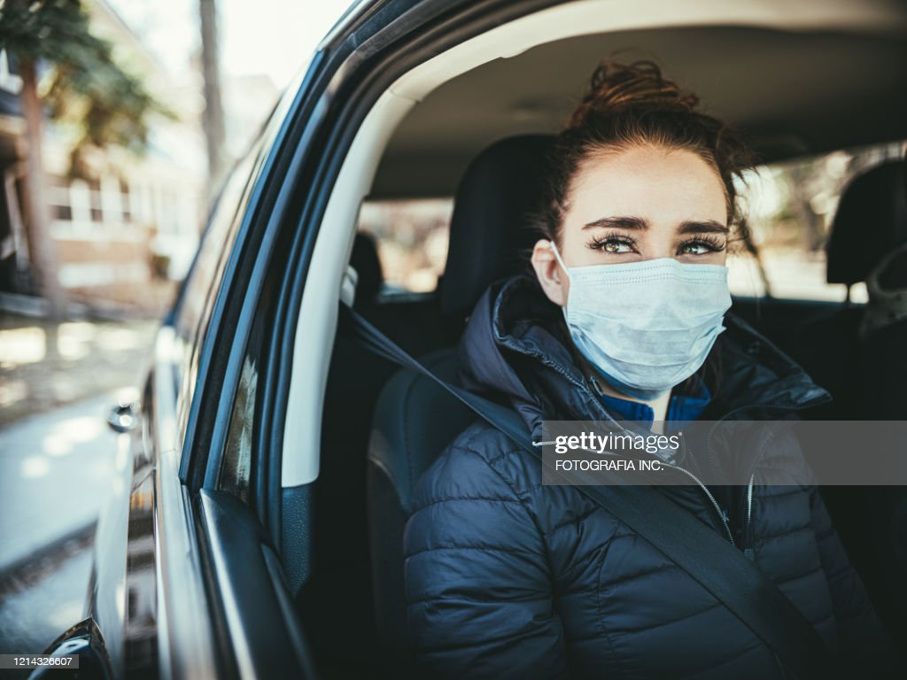 COVID-19, Young woman wearing disposable face mask while driving : Stock Photo