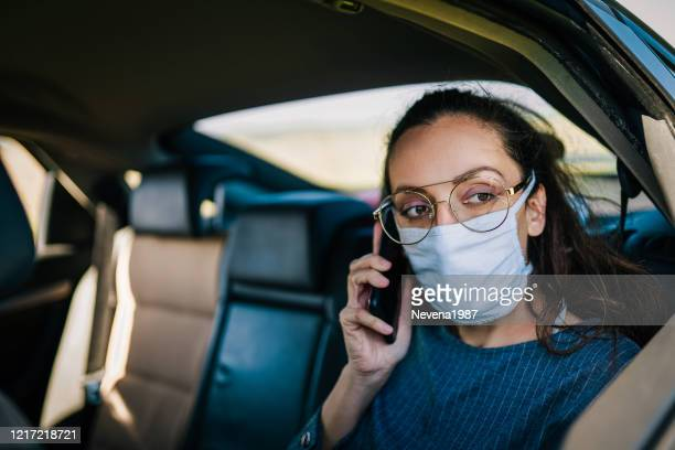 covid-19, young woman wearing disposable face mask while driving - car interior stock pictures, royalty-free photos & images