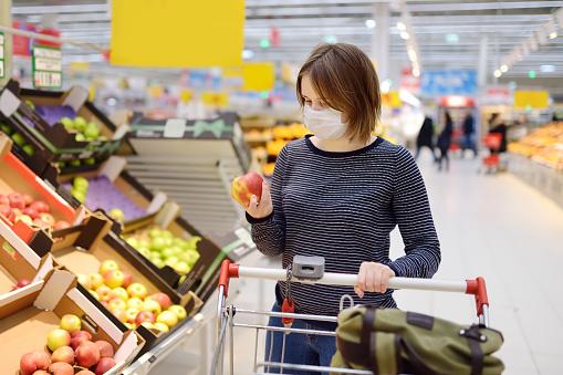Young woman wearing disposable medical mask shopping in supermarket during coronavirus pneumonia outbreak 1212922481
