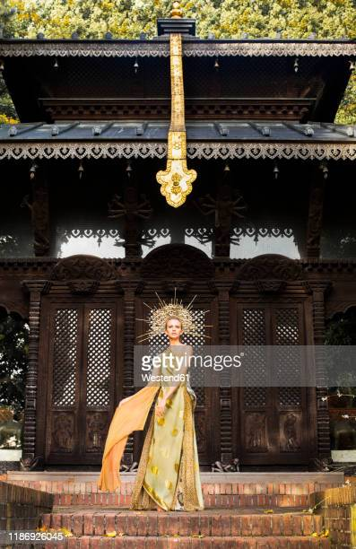 young woman wearing dress and headdress in front of a pagoda - headdress stock pictures, royalty-free photos & images