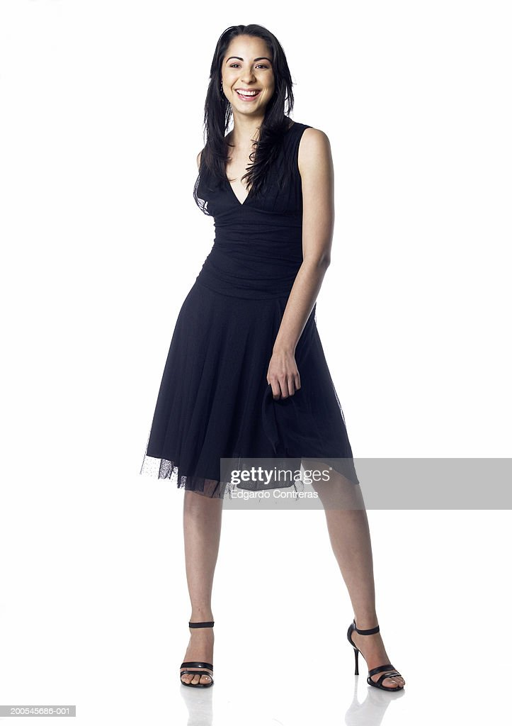 Young woman, wearing dress and high heels, smiling, portrait : Stock Photo