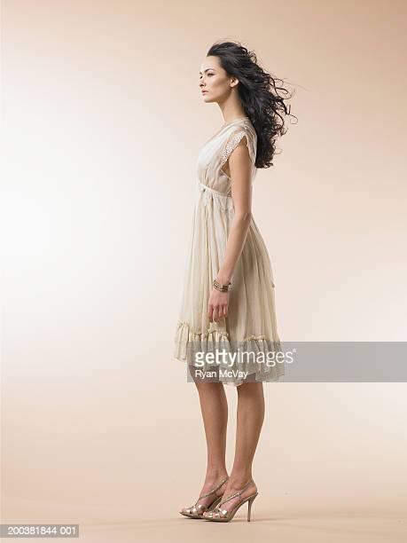 young woman wearing dress, side view - beige dress stock pictures, royalty-free photos & images