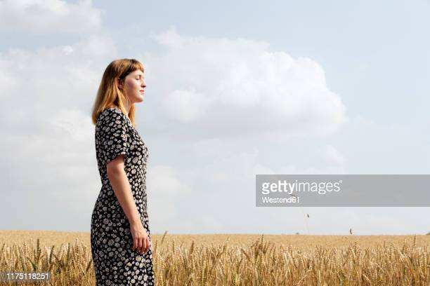 young woman wearing dress with floral design standing in grain field - floral pattern dress stock pictures, royalty-free photos & images