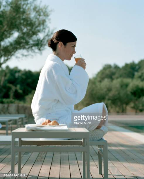 young woman wearing dressing gown having breakfast by swimming pool - three quarter length stock pictures, royalty-free photos & images