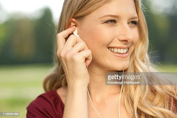 Young woman wearing ear buds, portrait