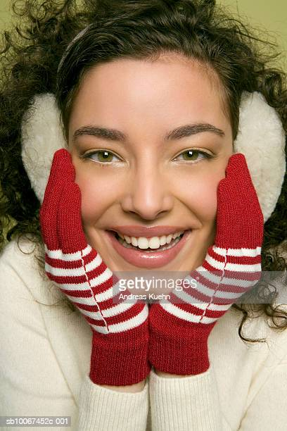 Young woman wearing ear muff, smiling, portrait, close-up