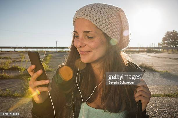 Young woman wearing earphones listening to music