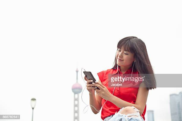 Young woman wearing earphones, looking at smartphone, Shanghai, China
