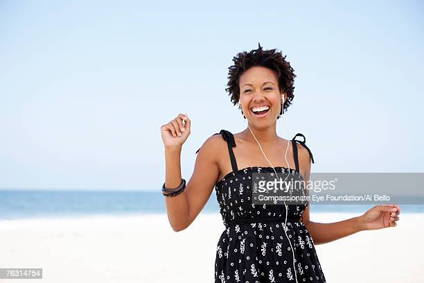 Young woman wearing earphones on beach, laughing, portrait, waist up