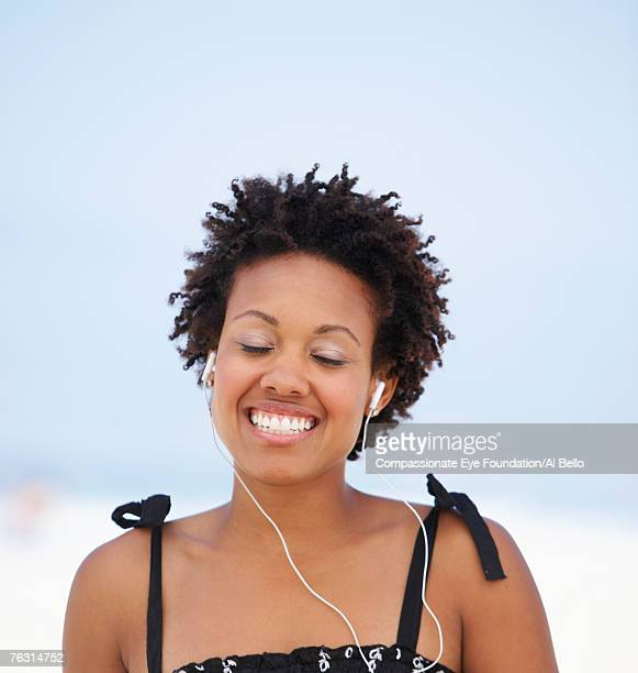 Young woman wearing earphones on beach, smiling with eyes shut