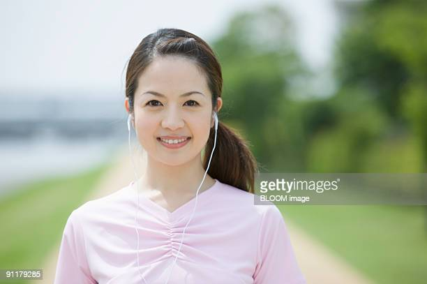 Young woman wearing earphones, smiling