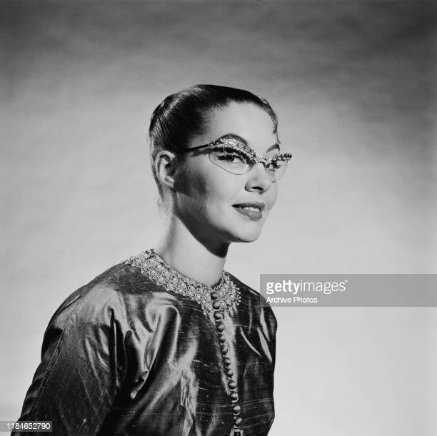 Young woman wearing elaborate jewelled cat's eye spectacles with an embroidered Asian-style jacket, 1956.