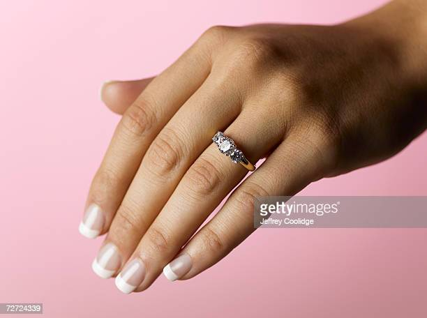 young woman wearing engagement ring, close up of hand (focus on ring) - anello gioiello foto e immagini stock