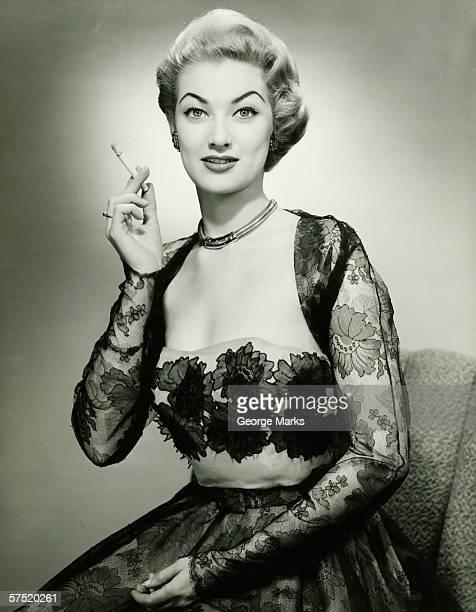 Young woman wearing evening dress smoking cigarette, (B&W), portrait