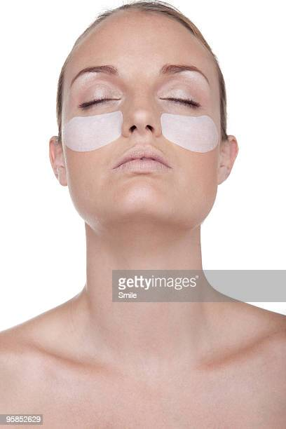 Young woman wearing eye lift patches