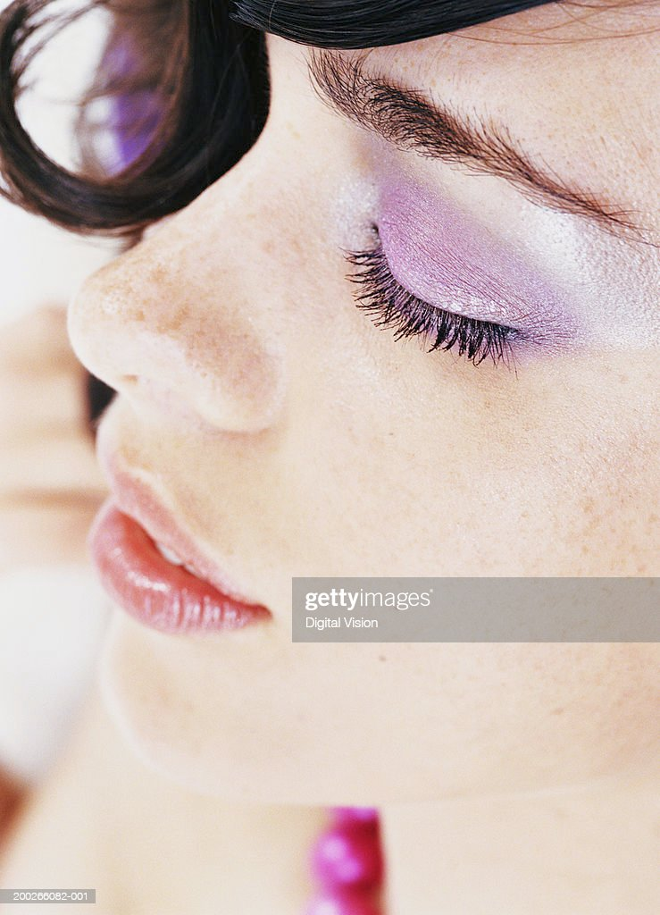 Young woman wearing eye make-up, lying down, eyes closed, close-up : Stock Photo