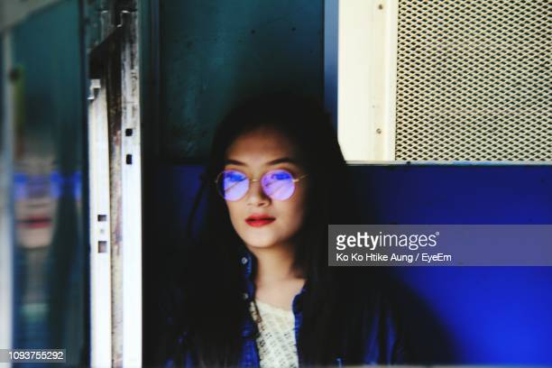 young woman wearing eyeglasses while sitting in train - ko ko htike aung stock pictures, royalty-free photos & images
