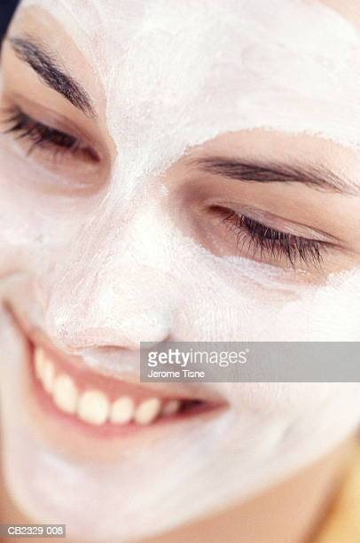 Young woman wearing face mask, smiling, close-up