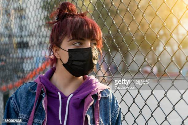 young woman wearing face mask stuck in quarantine covid-19 , corona virus - audience free event stock pictures, royalty-free photos & images