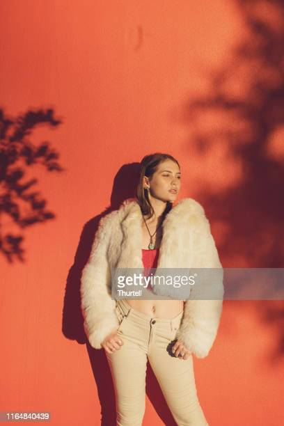 young woman wearing fake fur coat - womenswear stock pictures, royalty-free photos & images
